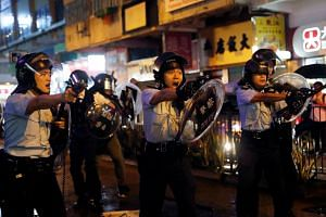 Police officers point their guns at protesters in Tseun Wan in Hong Kong on Aug 25, 2019.