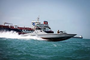 A boat of the Iranian Revolutionary Guard passes by the Stena Impero, a British-flagged oil tanker, which was seized by Iran as tensions flared in the Straits of Hormuz.