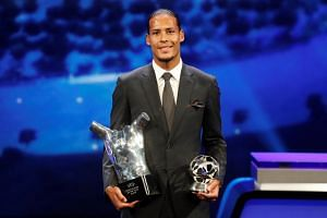 Liverpool's Virgil van Dijk with the Uefa Men's Player of the Year and Champions League Defender of the Season awards.