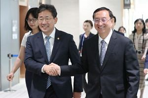 South Korean Culture Minister Park Yang-woo (left) and his Chinese counterpart Luo Shugang shake hands prior to their talks in Incheon, west of Seoul, South Korea, on Aug 29, 2019.