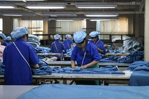 Workers producing cloth that will be exported to the US at a textile factory in Binzhou, China. Factory activity in China shrank in August for the fourth month in a row as the US ramped up trade pressure.