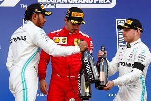 Leclerc celebrates on the podium (centre) with second-placed Hamilton (left) and third-placed Bottas.