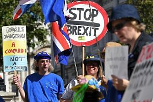Pro-EU supporters demonstrating outside the Cabinet Office in London yesterday. Britain's Prime Minister Boris Johnson is preparing for a showdown with MPs opposed to a no-deal Brexit when Parliament sits today.