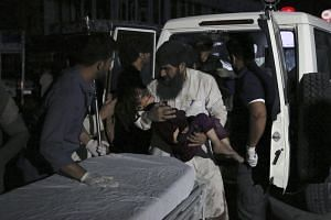 Afghan men carry an injured girl into the hospital after a large explosion in Kabul on Sept 2, 2019.
