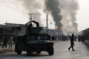 Policemen keep watch as angry Afghan protesters burn tyres and shout slogans at the site of a blast in Kabul, Afghanistan on Sept 3, 2019.