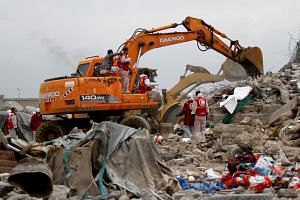 Red Crescent medics look on as an excavator is used to dig through rubble to search for bodies at the site of Saudi-led air strikes on a Houthi detention centre in Dhamar, Yemen.