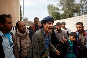 A family member of one of the victims of Saudi-led air strikes on a Houthi detention centre in Dhamar, Yemen, reacts during an interview with Reuters.