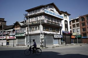In this photo taken on Aug 25, 2019, a man cycles past closed shops and hotels during restrictions in Srinagar, after scrapping of the special constitutional status for Kashmir by the Indian government.