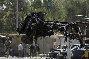 Resolute Support (RS) forces remove a destroyed vehicle after a car bomb explosion in Kabul.