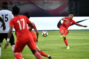 Top: Syahrul Sazali's free kick on the way into the net to seal Singapore's 2-0 win over Fiji in their Under-22 international at Bishan Stadium last night. Above: Singapore's Daniel Goh, who scored the opener, tussling with Fiji's Semi Wara. ST PHOTO