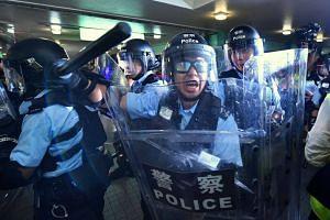 Hong Kong riot police clearing an overhead bridge in Sheung Shui, Hong Kong, on July 13, 2019.