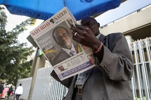 A Kenyan man reads a local newspaper with the headline reporting on Mugabe's death.