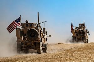 A US military convoy takes part in joint patrol with Turkish troops in the Syrian village of al-Hashisha.