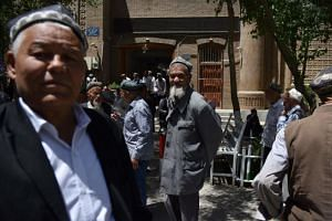 In a photo taken on May 31, Uighur men leave a mosque after prayers in Hotan in China's Xinjiang region.
