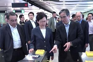 Chief Executive Carrie Lam touring the vandalised Central MTR station with officials. She examined electronic ticketing machines and boarded-up windows that were broken.