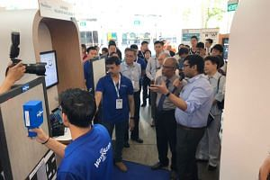 Minister for the Environment and Water Resources Masagos Zulkifli listening to an exhibitor for an energy intelligence technology firm at an A*Star event on Sept 10, 2019.