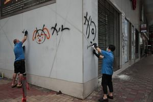 Workers remove graffiti left by protesters during a protest the night before in Hong Kong on Sept 1, 2019.