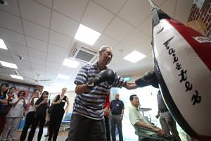 At Telok Blangah Senior Care Centre, seniors can take penalty shots and receive boxing lessons, all part of an effort to help them overcome their reluctance to continue with their rehabilitation.