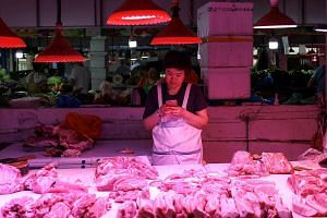 A vendor waits for customers at a pork stall in a market in Beijing on Sept 5, 2019.