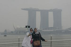 Tourists from Jakarta, Ms Novi Iryani, 36 (left) and Ms Ninis Rais, 44, take a selfie with Marina Bay Sands shrouded in haze in the background at around 2pm on Sept 14, 2019.