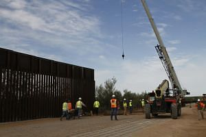 Workers at a border wall construction site in New Mexico, on Aug 23, 2019. Savings weren't sufficient to pay for an additional 32km of wall in Arizona and California.
