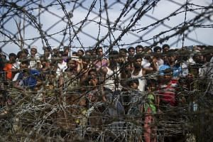 In a photo taken on April 25, 2018, Rohingya refugees gather behind a barbed-wire fence in a temporary settlement in Rakhine, Myanmar.