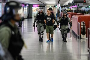 In this photo taken on Sept 8, 2019, riot police escort a man inside the Central MTR station in Hong Kong.