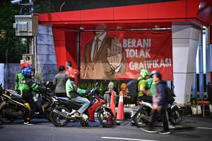"""A banner with the slogan """"Dare to not receive gratification"""" outside the KPK building on April 5, 2019."""