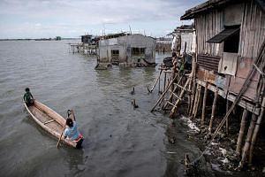 A photo taken on Feb 3 shows residents using a boat to travel across the water in Sitio Pariahan, in the Philippines' Bulacan province, which has sunk 4-6cm a year since 2003, according to satellite monitoring.