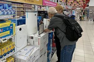 Shoppers looking at air purifiers at FairPrice Xtra.