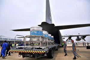 Members of the Royal Malaysian Air Force loading a Hercules C-130 aircraft with salt solutions yesterday for cloud-seeding operations that are being carried out from the air force's Kuching airbase in Sarawak. The Air Pollutant Index in the state's S