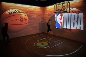 A photo taken on Aug 19 shows visitors playing basketball at the NBA exhibition in Beijing.