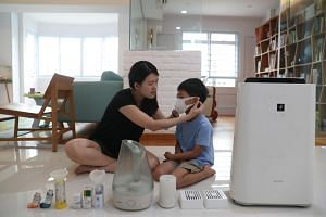 Ms Suwanti Tan, 32, putting a facial mask on her son Lucas Zhang, with all the asthma equipment in the foreground.