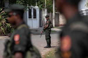 In a photo from May 1, 2019, soldiers stand guard outside St Sebastian Church, days after a string of suicide bomb attacks across the island on Easter Sunday in Negombo, Sri Lanka.