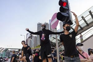 Masked protesters walk to Kowloon station to take part in a protest event in Hong Kong on Sept 22, 2019.