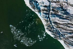 A photo taken on Aug 17 shows an aerial view of bergy bits and growlers floating on the south-eastern shore of Greenland. The report says ice loss from Greenland and Antarctica is speeding up and is expected to accelerate from the middle of this cent