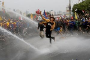 Student protesters hurl objects as they are sprayed by a police water cannon truck during a protest in Jakarta, Indonesia, on Sept 24, 2019.
