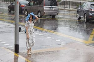 A woman shelters from the rain around the central area of Singapore, on Sept 24, 2019.