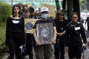 In a photo taken on Sept 21, protesters march during a global climate strike named Earth Funeral in Taipei.