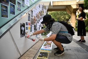 A protester puts up Post-it notes and posters in their attempt to rebuild the Lennon Walls that were torn down by pro-Beijing activists last weekend, in Hong Kong on Sept 28, 2019.