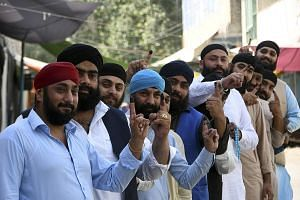 Afghan Sikhs showing their inked fingers after casting their votes yesterday at a polling station in the city of Jalalabad, east of Kabul. There are fears that a deeply flawed election and contested result could drive Afghanistan into further chaos.