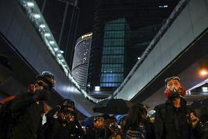 Protesters wearing gas masks as they seek shelter with umbrellas during a rally commemorating the 5th anniversary of the 'Umbrella Revolution' in Hong Kong, on Sept 28, 2019.