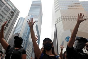 Anti-government protesters raise their hands up as they demonstrate at Causeway Bay district in Hong Kong, on Sept 29, 2019.
