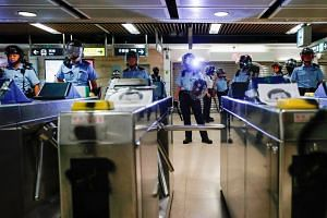 Riot police stand guard inside Sha Tin MTR station as anti-government protesters gather to demonstrate against the railway operator, on Sept 25, 2019.