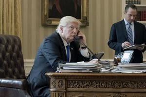 A photo taken on Jan 28, 2017, shows US President Donald Trump on the phone with Russian President Vladimir Putin, in the Oval Office of the White House in Washington.