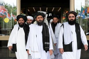 In a photo taken on May 30, 2019, members of a Taleban delegation, led by chief negotiator Mullah Abdul Ghani Baradar (centre), leave after peace talks with Afghan senior politicians in Moscow, Russia.