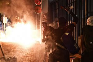 Protesters throw a petrol bomb at a police station in Tsuen Wan, Hong Kong on Oct 2, 2019.
