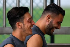 In a photo taken on July 25, 2018, Arsenal players Mesut Ozil (left) and Sead Kolasinac arrive for a team training session during the International Champions Cup match in Singapore.