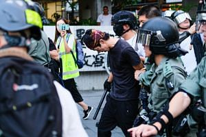 Riot police arrest a demonstrator during an anti-government protest against the mask ban, on Oct 6, 2019.