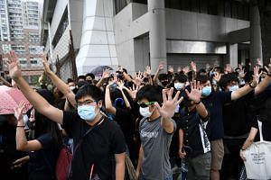 Protesters shout slogans as they gather outside the Eastern District Courts in Hong Kong, on Oct 7, 2019, where the first protesters arrested for wearing face masks appeared in court.